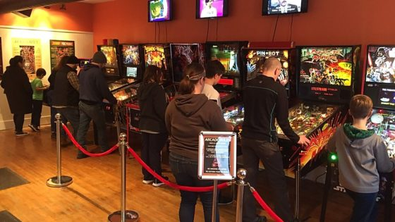 The front room of Pinball Land - pinball machines and people